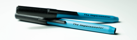 "Studio product shot of two of SLEEK USA's ""The Impersonator"" one-hitter, concealable smoking pens without product packaging"