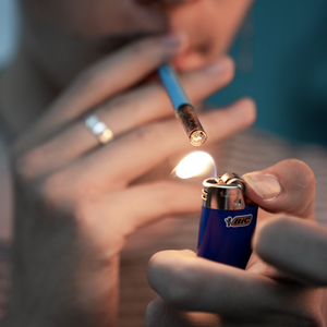 "SLEEK USA's ""The Impersonator"" one-hitter, concealable smoking pen being held up to the lips and between the pointer and middle finger of the male model's right hand, as he uses his left hand to light the chillum"