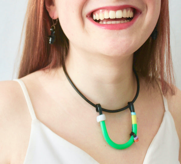 Sadye is wearing the Black with Green, White and Colours Uline on a fine leather cord that hangs 40cm with black Loopt earrings.