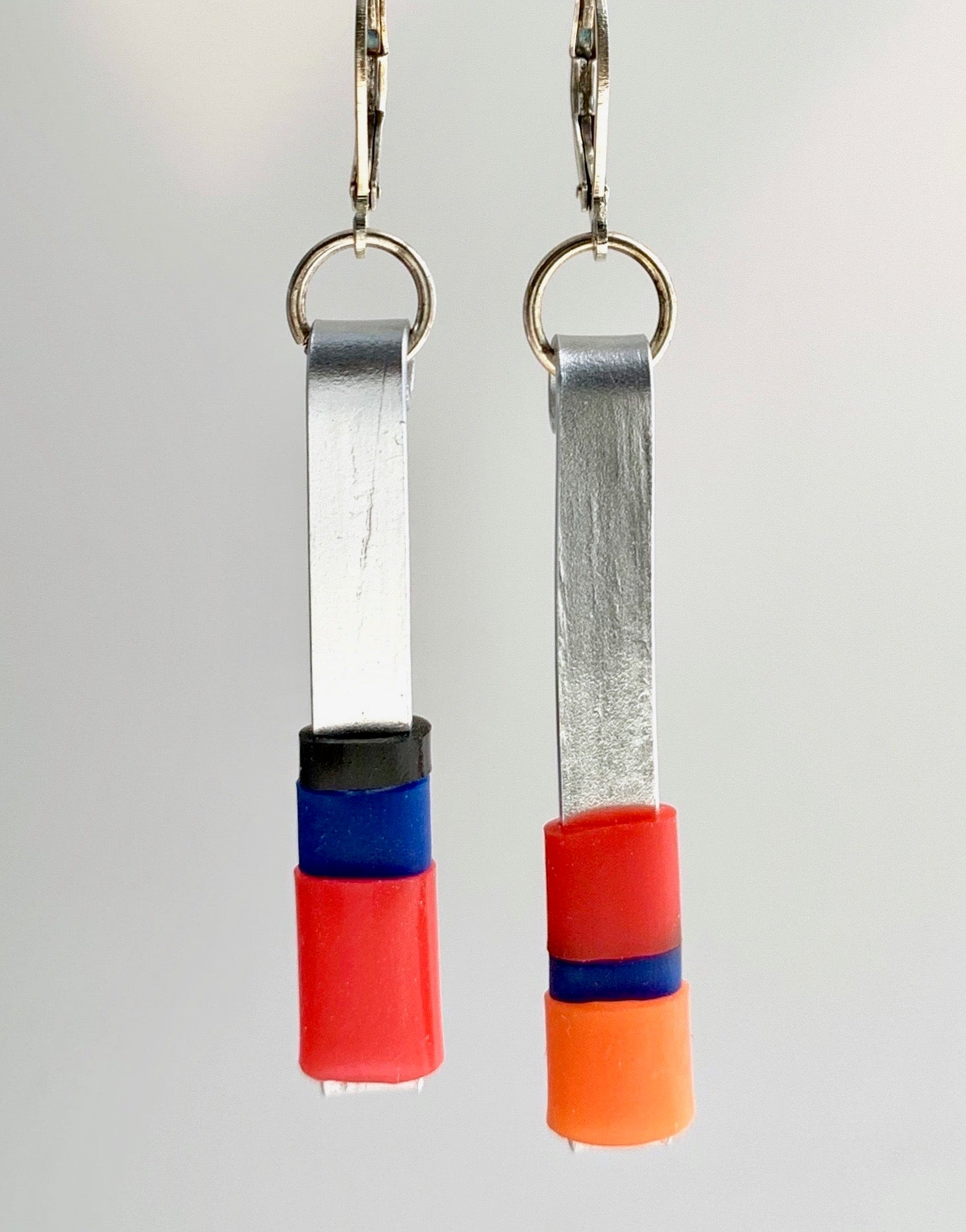 Matchstick earrings in silver coloured aluminum wire with red, orange, royal blue and black coloured silicone tubing. These hang 4.5cm in length.