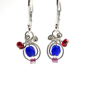 Silver coated copper wire with irridescent royal glass beads with red and purple glass accents. They have leverback hooks and hang a hair past a 1cm long.