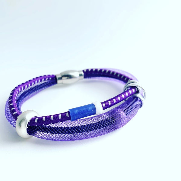 This Bracelet has netted tubing with two different kinds of shock cord, aluminum wire, mixed beads and silicon tubing with a magnetic clasp. It is 20cm.