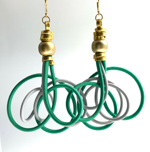 These Interloopt earrings in green, gray and gold and are made with shock cord and gold coloured aluminum wire with a gold plastic bead and leverback hooks. They hang 10cm long and are 6.5cm wide.