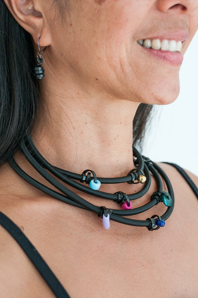 Arvi is wearing 170cm Loopt necklace/bracelet in heavy cord with thin black wire with mixed coloured beads, worn 4x around her neck. She is also wearing matching Loopt earrings in thin black.