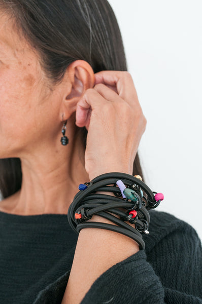 Arvie is wearing a 170cm Loopt in heavy cord with thin black wire with mixed coloured beads as a bracelet. She is also wearing thin black Loopt earrings.