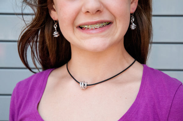 Bella is wearing Loopt earrings and Rubber Loopt necklace both in round silver