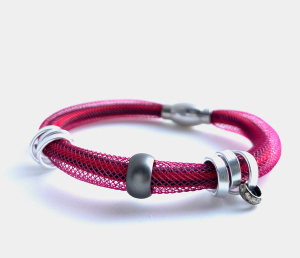 This Bracelet has netted tubing with shock cord, aluminum wire and a coloured bead with a magnetic clasp. It is 21cm.
