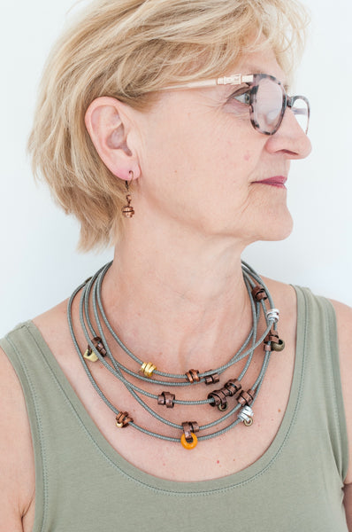 Beverly is wearing 2 112cm Loopt necklaces. Both in fine taupe cord. One with flat bronze wire and mixed neutral coloured beads and the other in mixed thin wire. Beverly is also wearing thin bronze Loopt earrings.