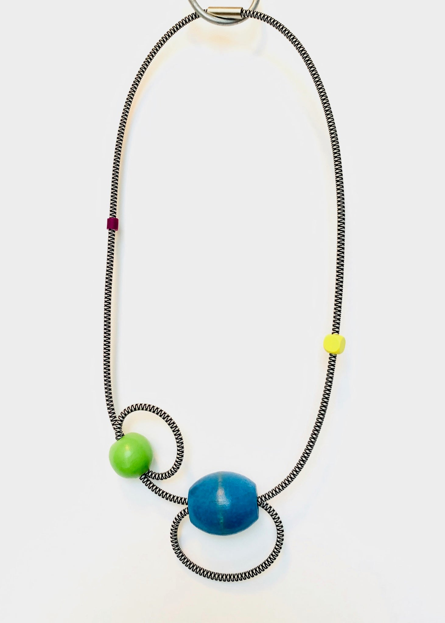 This necklace hangs 55cm long. It is made with black and white shock cord, a large vintage blue wooden bead, green+yellow wooden beads and purple silicone tubung bead.