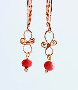 Gold coloured copper wire with small  faceted red glass bead. They have leverback hooks and hangs 1.5cm long.