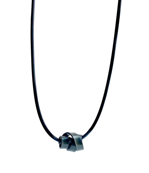 This Rubber Loopt necklace is in flat black coloured aluminum wire. It hangs on a rubber necklace with an interlocking closure. This piece comes in many variations.
