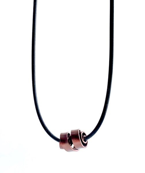 This Rubber Loopt necklace is in flat bronze coloured aluminum wire. It hangs on a rubber necklace with an interlocking closure. This piece comes in many variations.