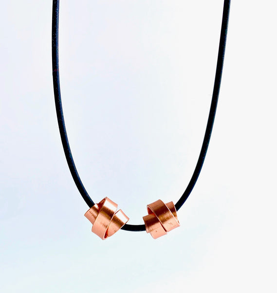 This Rubber Loopt necklace is made of aluminum wire in copper colour. Thes 2 wire pieces can be moved together or apart. It hangs on a rubber necklace with an interlocking clasp.