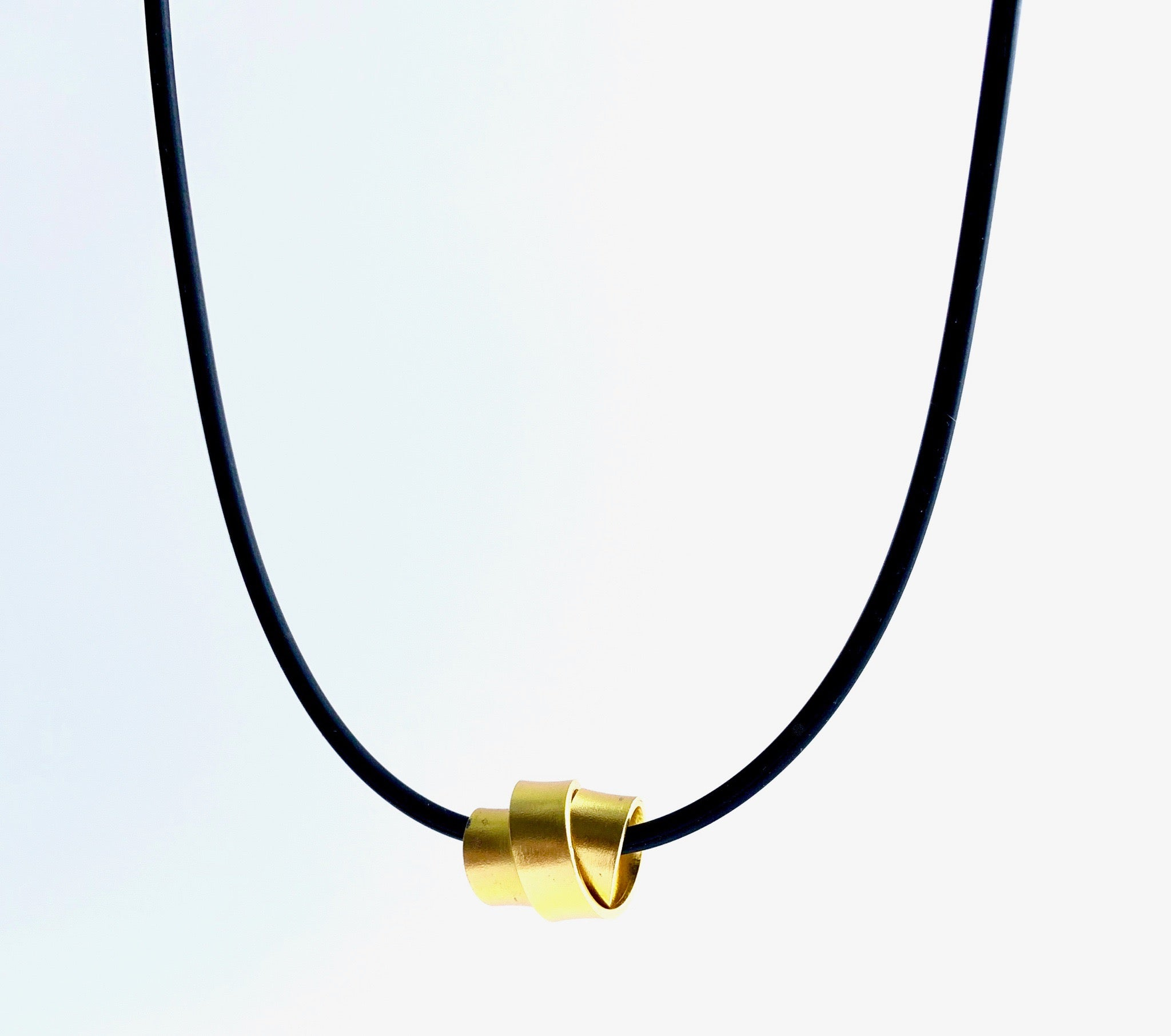 This Rubber Loopt necklace is in flat gold. Made of aluminum wire and hangs on a rubber necklace with an interlocking closure. This piece comes in many variations.