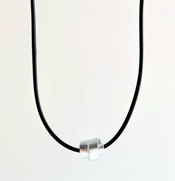 This Rubber Loopt necklace is in flat silver aluminum wire. It hangs on a rubber necklace with an interlocking closure. This piece comes in many variations.
