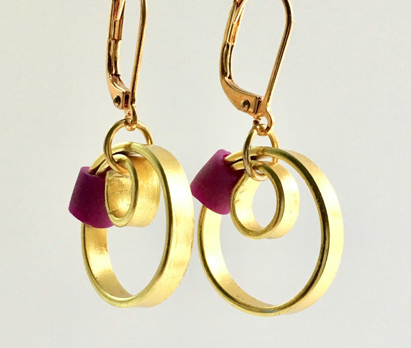 These Reel Earrings are made of gold coloured aluminum wire with added purple silicone beads. All Earrings sport non nickel leverback hooks unless noted otherwise.