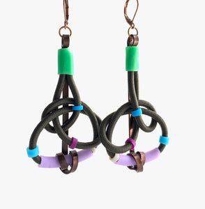 These earrings are made with shock cord bronze coloured aluminum wire, silicone tubing and leverback hooks. They hang 7.5 cm long and are nearly 4cm wide.
