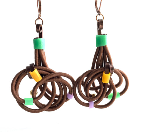 These earrings are made with shock cord bronze coloured aluminum wire, silicone tubing and leverback hooks. They hang 7.5 cm long and are 4.5cm wide.