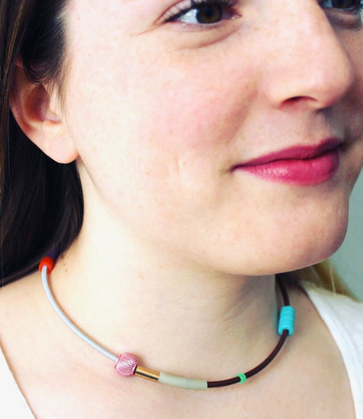 Isabelle wears Colour Collage choker in lt. gray+brown with  pink and turq. beads.