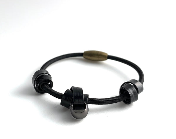 A Loopt bracelet in flat black on a thin cord.