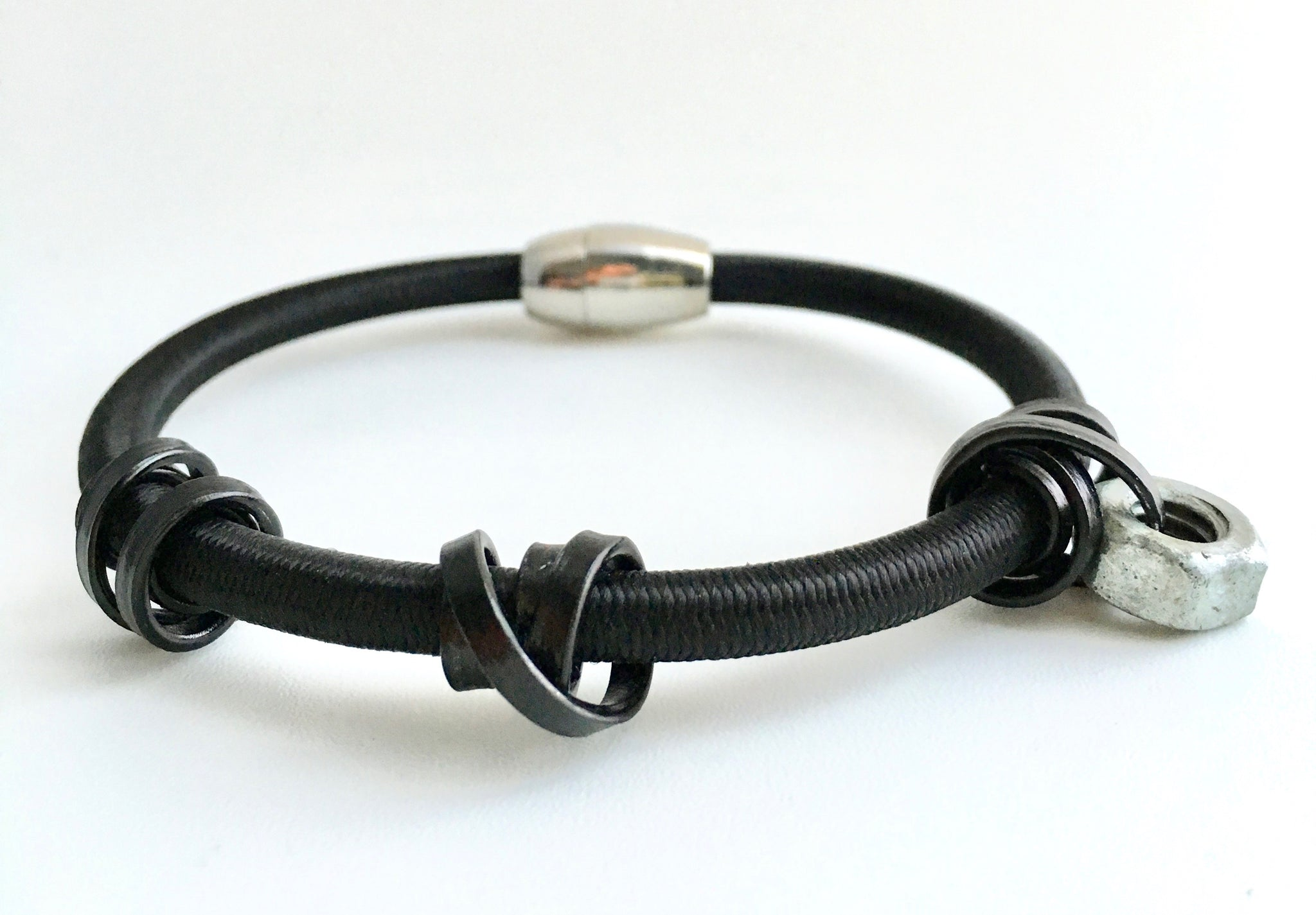 A Loopt bracelet in thin black aluminum coloured wire on heavy cord.