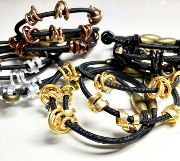Mix of Loopt bracelets on fine cord in round and thin aluminum wire.