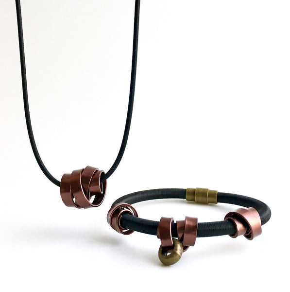A Rubber Loopt in flat bronze and a Loopt bracelet in flat bronze on a heavy cord.