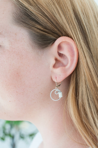 Isabelle is wearing Reel earrings in silver with white