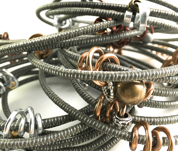 Mix of many Loopt necklace/bracelets in fine taupe with thin and round silver and bronze coloured aluminum wire.