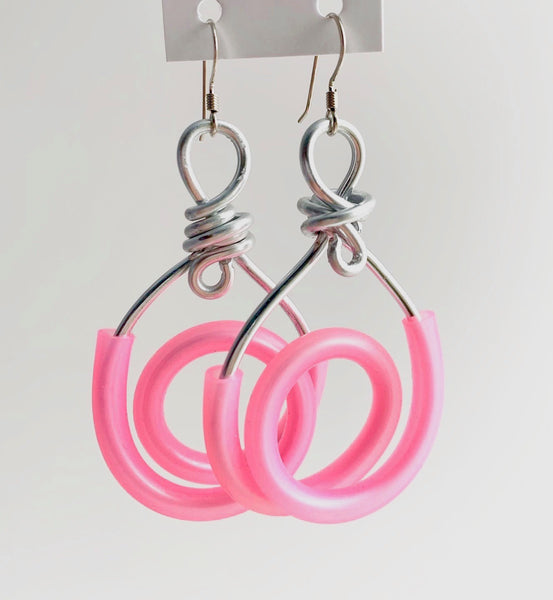 These coil earrings are made from silver aluminum wire and pink silicone tubing. These have non nickel fish hooks with rubber stoppers.