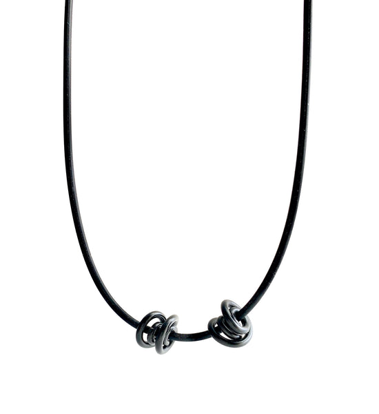 This Rubber Loopt necklace is in round black. Made of aluminum wire and hangs on a rubber necklace with an interlocking closure. This piece comes in many variations.