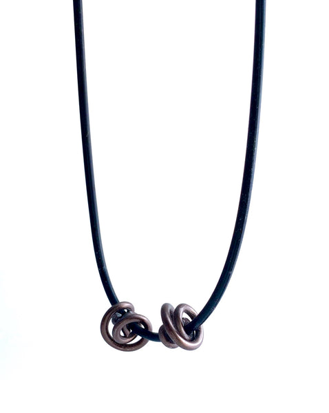 This Rubber Loopt necklace is in round bronze. Made of aluminum wire and hangs on a rubber necklace with an interlocking closure. This piece comes in many variations.