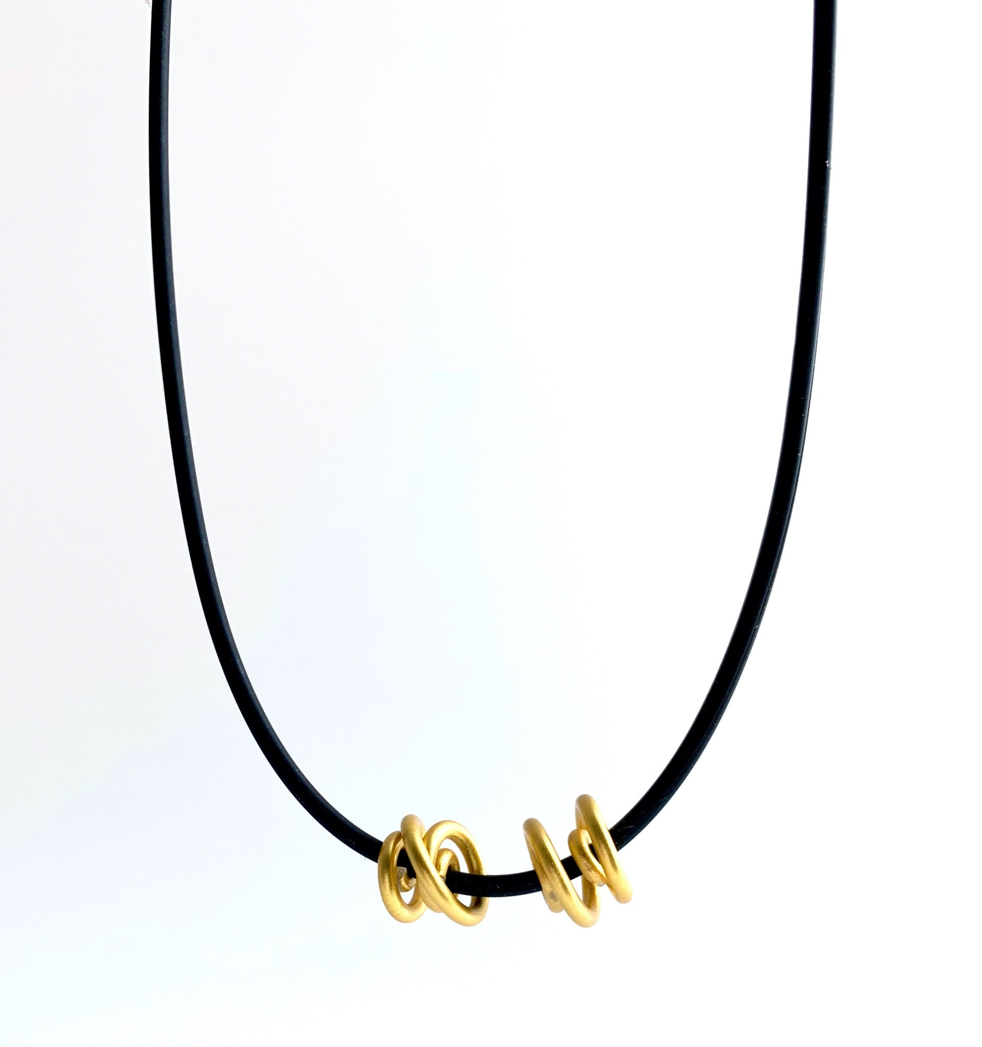 This Rubber Loopt necklace is in round gold. Made of aluminum wire and hangs on a rubber necklace with an interlocking closure. This piece comes in many variations.