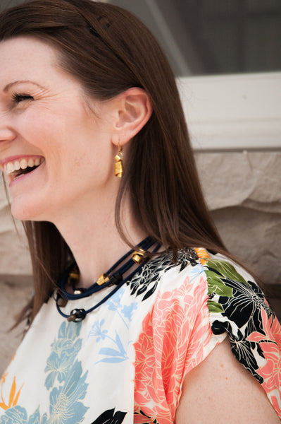 Sarah is wearing Flat Loopt Earrings in gold and a fine Loopt necklace/bracelet in navy and gold.