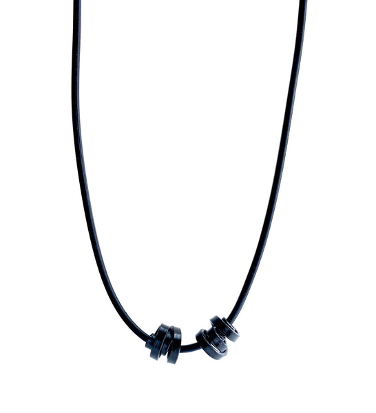 This Rubber Loopt necklace is in thin black. Made of aluminum wire and hangs on a rubber necklace with an interlocking closure. This piece comes in many variations.