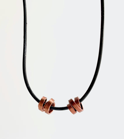 This Rubber Loopt necklace is in thin bronze. Made of aluminum wire and hangs on a rubber necklace with an interlocking closure. This piece comes in many variations.
