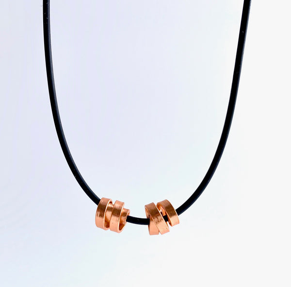 This Rubber Loopt necklace is in thin copper. Made of aluminum wire and hangs on a rubber necklace with an interlocking closure. This piece comes in many variations.