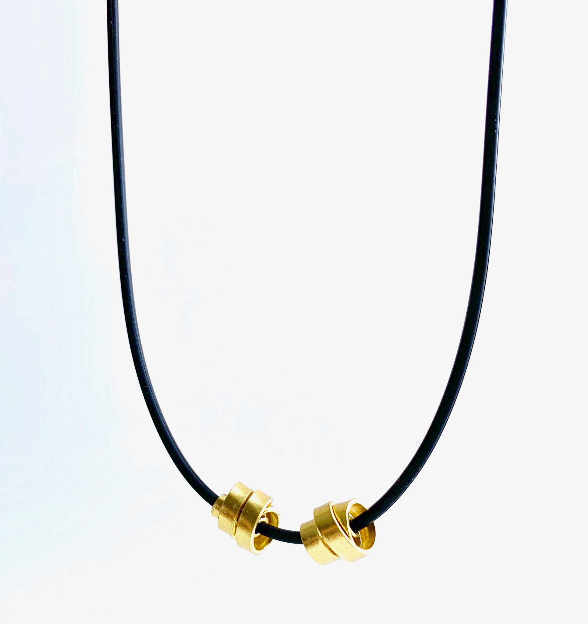 This Rubber Loopt necklace is in thin gold. Made of aluminum wire and hangs on a rubber necklace with an interlocking closure. This piece comes in many variations.