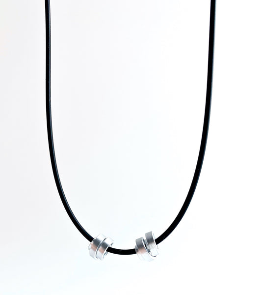 This Rubber Loopt necklace is in thin silver. Made of aluminum wire and hangs on a rubber necklace with an interlocking closure. This piece comes in many variations.