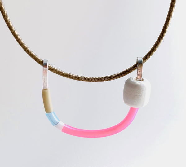 This Uline necklace hangs on a beige shock cord with a magnetic clasp that is 46cm in length.