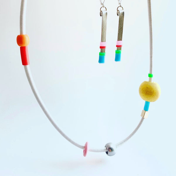 This piece is made with 5mm white shock cord and hangs 63cm long. It is paired here with matchstick earrings. Sold separately.