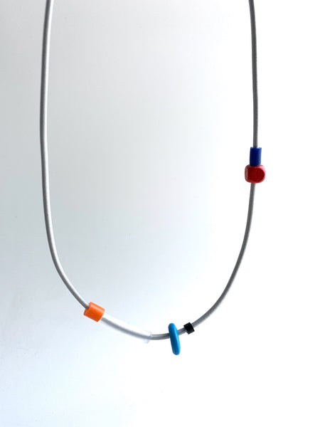 This necklace is made with shock cord silcone and wood beads. It has an interlocking magnetic clasp and hangs 46cm long.