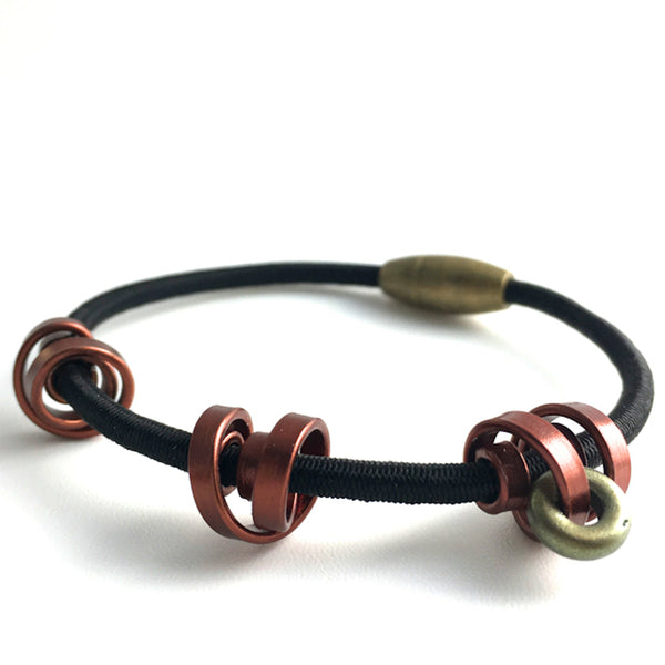 A Loopt bracelet on fine cord in thin bronze coloured aluminum wire.
