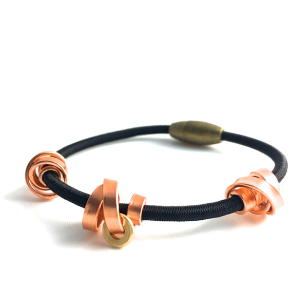 This is a Loopt bracelet on a fine cord and thin copper coloured aluminum wire. All bracelets sport magnetic clasps.