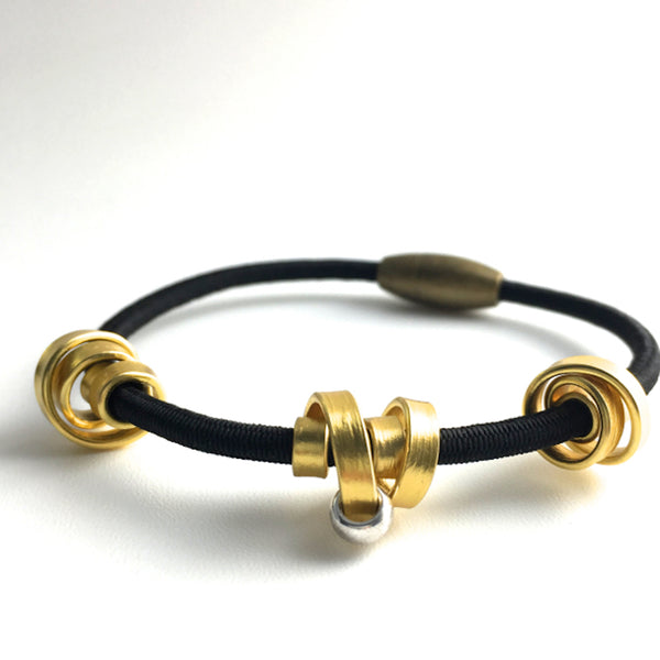This is a Loopt bracelet on a fine cord and thin gold coloured aluminum wire. All bracelets sport magnetic clasps.