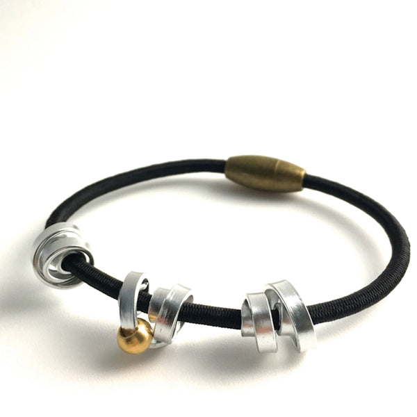 This is a Loopt bracelet on a fine cord and thin silver coloured aluminum wire. All bracelets sport magnetic clasps.