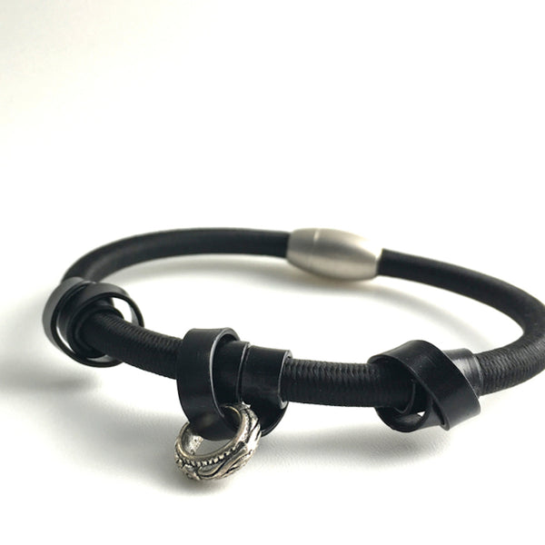 A Loopt bracelet in flat black aluminum coloured wire on heavy cord.