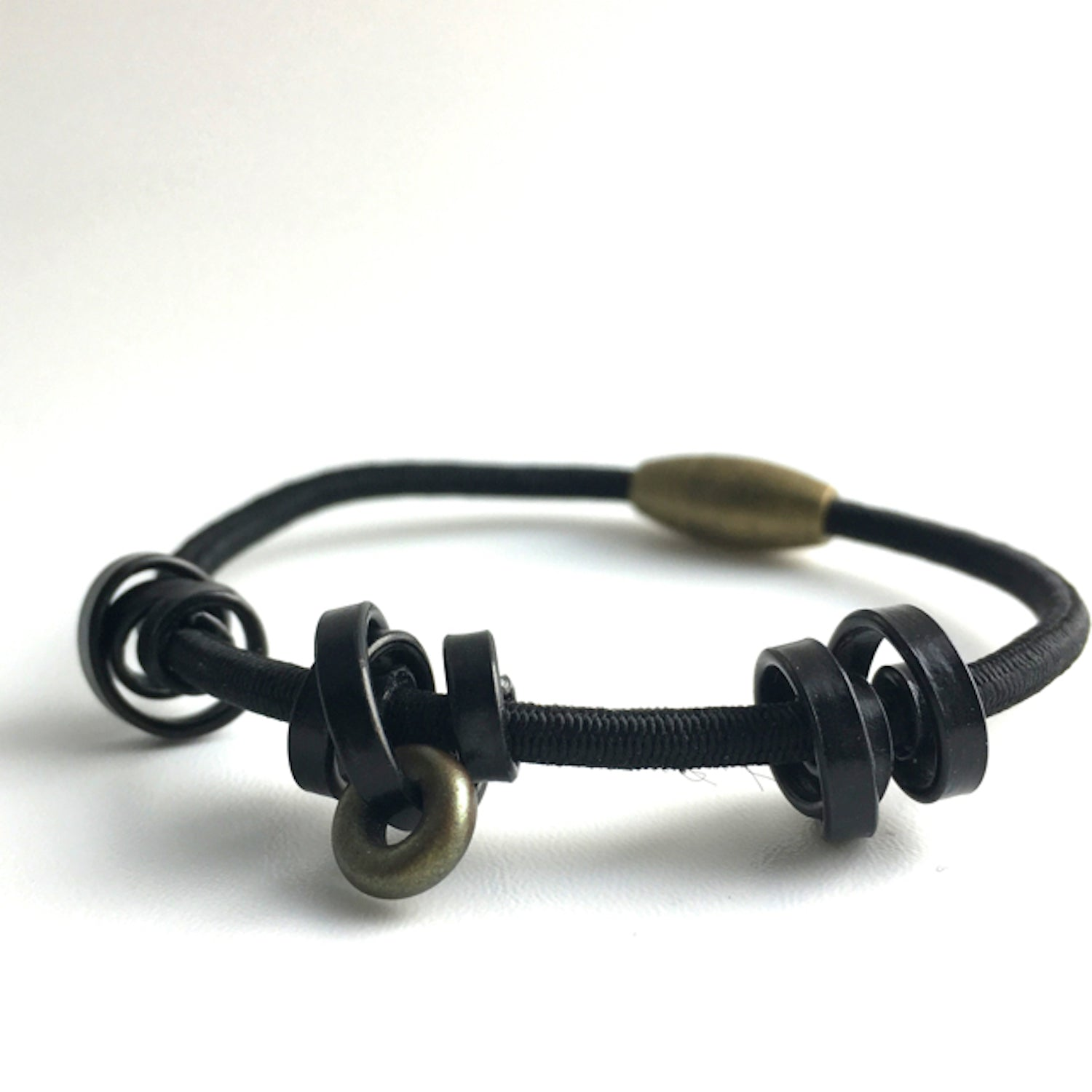 This is a Loopt bracelet on a fine cord and thin black coloured aluminum wire. All bracelets sport magnetic clasps.