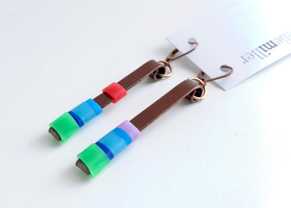 Matchstick earrings in bronze coloured aluminum wire with green, mix of blues, red and lavender coloured silicone tubing. These hang 4.5cm in length.