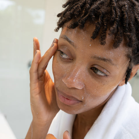 a young female is exfoliating her face with cure aqua gel